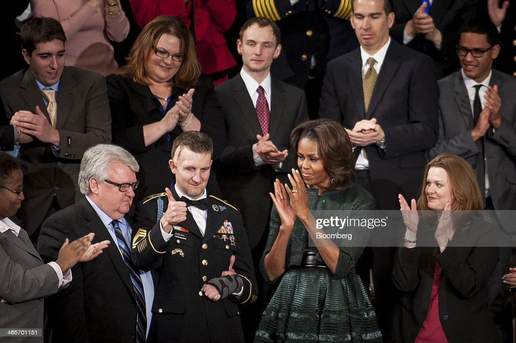 US Army Ranger Sergeant First Class Cory Remsburg, bottom row center left, gives a thumbs as he receives a standing ovation by First Lady Michelle Obama, center right, and the entire Congress as U.S. President Barack Obama, unseen, tells his story during the State of the Union address to a joint session of Congress at the Capitol in Washington, D.C., U.S., on Tuesday, Jan. 28, 2014. President Barack Obama urged Congress to back two priorities for U.S. multinational corporations: broader authority for his administration to negotiate trade deals, and changes to immigration laws. Photographer: Pete Marovich/Bloomberg via Getty Images