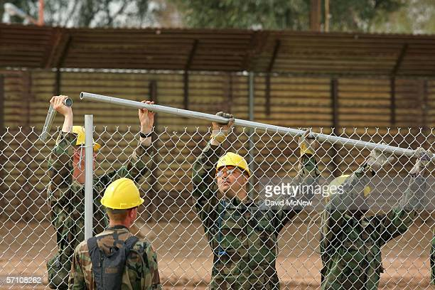 S Army Rangers erect a chainlink fence that will be topped with barbed wire parallel to the primary steel US/Mexico border fence to further fortify...