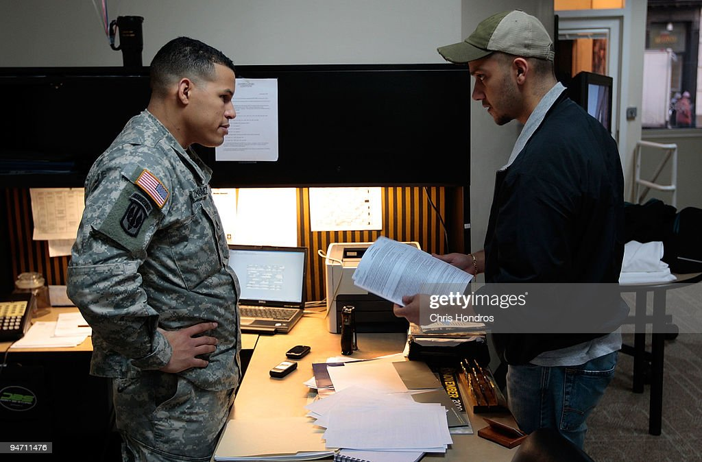 Army recruiter Staff Sgt Pablo Valdez Martinez chats about paperwork requirements with a potential Army recruit in the new office for the City Hall...