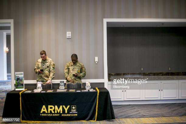 US Army recruiters view mobile devices during a National Career Fairs event in Dearborn Michigan US on Tuesday Dec 5 2017 The US Department of Labor...