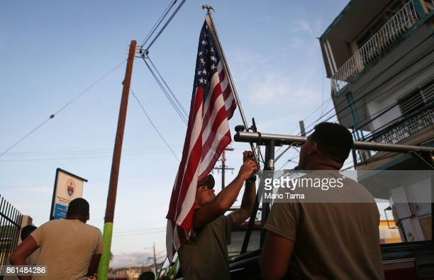 S Army reserve soldiers from Puerto Rico attach an American flag to one of their vehicles in an area with a sporadic electricity supply on October 14...