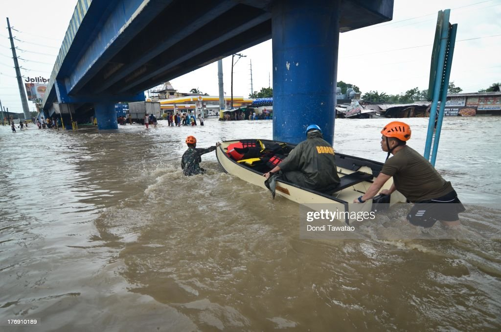 Army reservists use a boat to pass through floodwaters that inundated parts of Las Pinas on August 19, 2013 in Las Pinas City south of Manila, Philippines. Tropical storm Trami which was enhanced by monsoon rains swept overnight through the southern metropolitan cities of Manila and leaving huge parts of four provinces underwater forcing residents to evacuate their homes and seek shelter in evacuation centers. At least three fatalities were recorded with thousands more still needing to be rescued.
