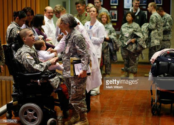 S Army Sergeant Juan RoldanJaramillo holds his 9 month daughter Bryana while greeting staff members at Walter Reed Medical Center after recieving a...