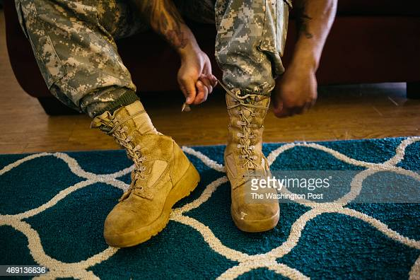 Army Sergeant Shane Ortega laces up boots before posing for a portrait at home at Wheeler Army Airfield on March 26 2015 in Wahiawa Hawaii