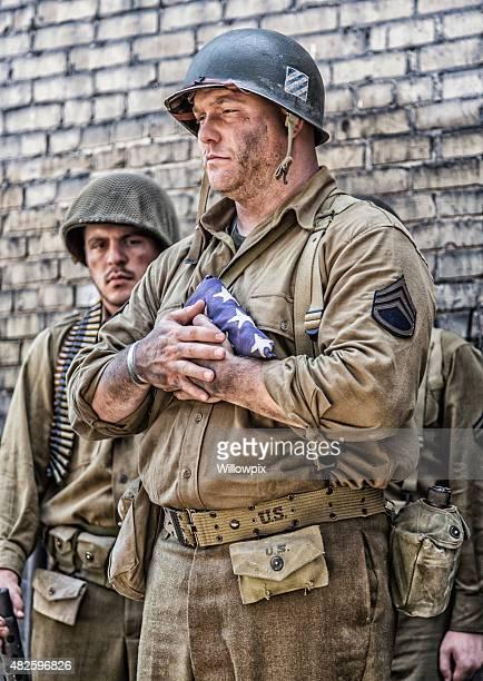 Américaine de la Seconde Guerre mondiale, l'armée Sergent Main tenant un drapeau à revers