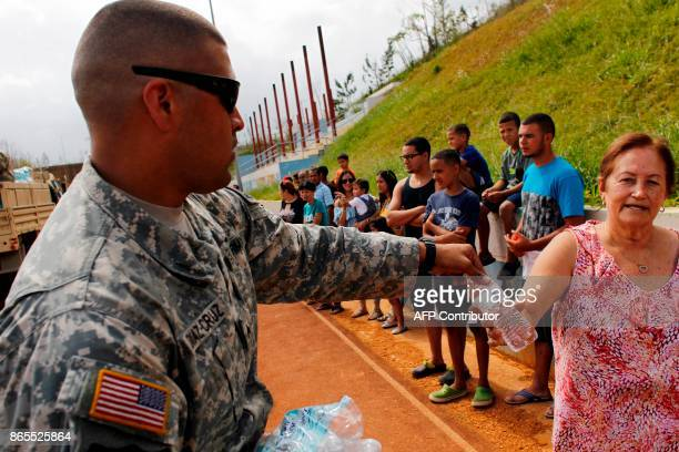 Army serviceman gives bottled water to residents affected by the passing of Hurricane Maria in Barranquitas Puerto Rico October 23 2017 / AFP PHOTO /...