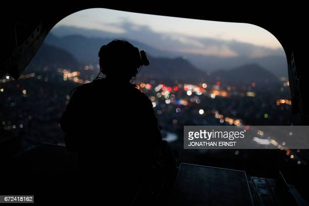 Army serviceman sits at the tailgate of an helicopter carrying US Defence Secretary after leaving the Resolute Support headquarters in the Afghan...