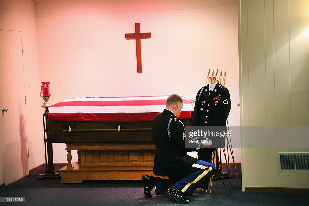 U.S. Army Sgt. Brant Sharp adjusts the uniform of Pfc. Aaron Toppen before it is transported along with his casket from Vandenberg Funeral Home to Parkview Christian Church for visitation on June 23, 2014 in Mokena, Illinois. Toppen, 19, was killed alongside four other American soldiers and an Afghan soldier in a friendly fire airstrike while they were engaged in a firefight earlier this month in Afghanistan. Sharp, who is attached to the same unit as Toppen, is assigned to be a constant escort for Toppens remains until burial on Tuesday.