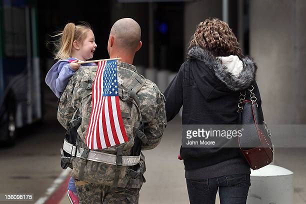 S Army Sgt Derek James walks with his daughter Avan James and his wife Madison James after his arrival at the Dallas/Fort Worth International Airport...