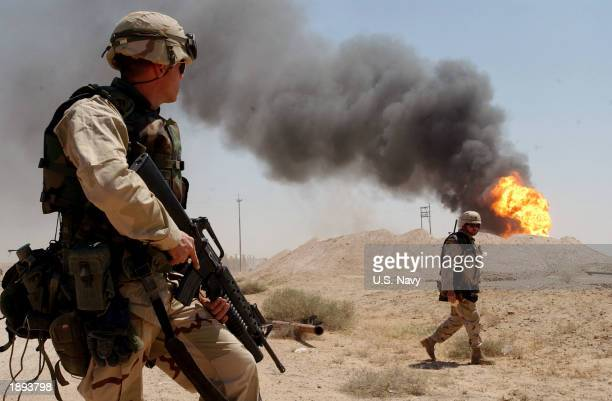 S Army Sgt Mark Phiffer stands guard duty April 2 2003 near a burning oil well in the Rumaylah Oil Fields in Southern Iraq Coalition forces have...