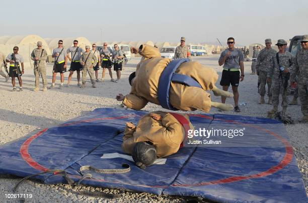 S Army Sgt Richard Hamburg jumps on a friend while sumo wrestling with a friend during an Independence Day BBQ for troops at Kandahar Airfield July 4...
