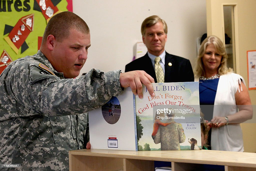 U.S. Army Sgt. Wesley Watkins of Union Bridge, Maryland, reads from Jill Biden's 'Don't Forget, God Bless Our Troops' as Virginia Gov. Bob McDonnell (C) and his wife Maureen McDonnell visit the KinderCare Learning Center August 9, 2012 in Alexandria, Virginia. A 21-year veteran of the U.S. Army, Gov. McDonnell's visit to the center is part of KinderCare's Honoring the Troops program taking place at the end of August in Virginia and Maryland.