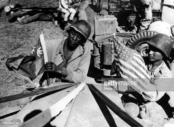 Army soldier and a Chinese soldier place a flag of their ally on their jeep before crossing the China border en route from Ledo to Kunming over the...