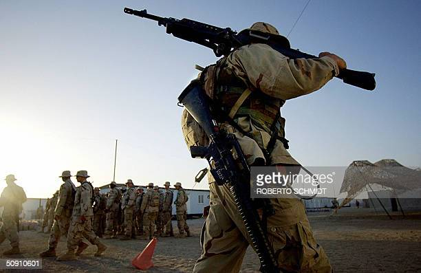 Army soldier from 2nd Brigade 12 Cavalry Regiment 1st Cavalry Division carries a M240 high caliber machine gun as he walks past soldiers getting...