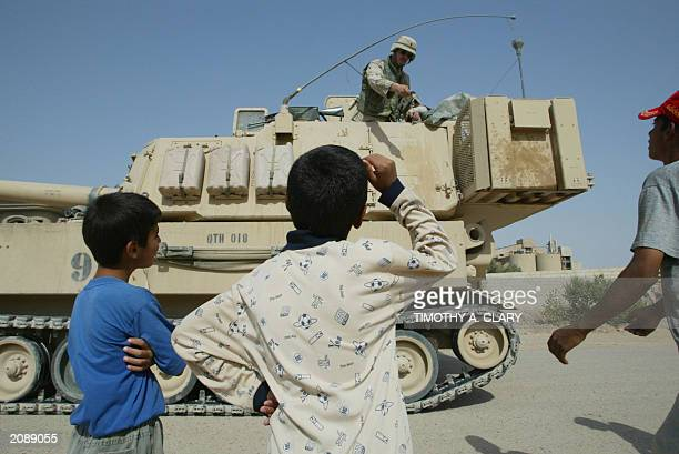 Army soldier hands a pack of chewing gum to Iraqi children 10 June 2003 as he patrols the flashpoint town of Fallujah 50 kms west of Baghdad US...