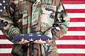 US Army soldier holding country flag by Stars and Stripes