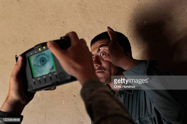 Army soldier in the 171 Cavalry scans the eye of an Afghan National Police member for identification purposes with a handheld biometric device June...