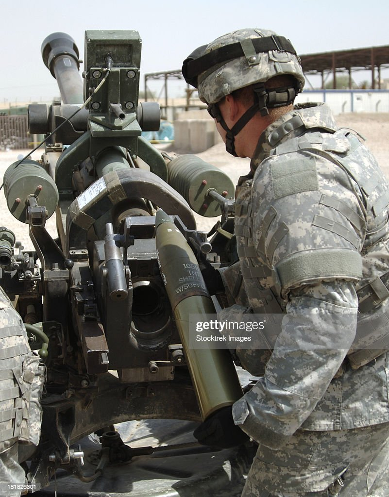 U.S. Army Soldier loads a 105mm artillery round into a M119 Howitzer.