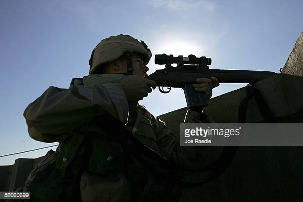 S Army soldier of the 1st Battalion 503rd Infantry Regiment takes a roof top sniper position during a joint patrol with Iraqi commandos as they...