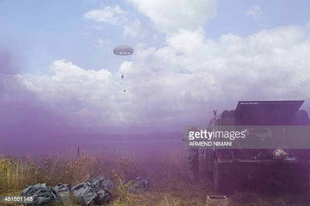 A US army soldier of the second Squadron 38th Cavalry Regiment part of the NATOled peacekeeping mission in Kosovo KFOR jumps with parachute as other...