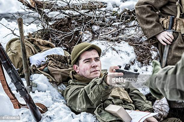 WWII US Army Soldier Passing Film Camera To Foxhole Buddy