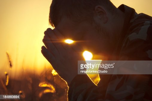 Army Soldier Praying Outside in Field at Sunset