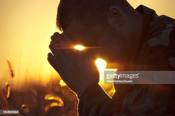 Soldat prier à l'extérieur dans le champ au coucher du soleil