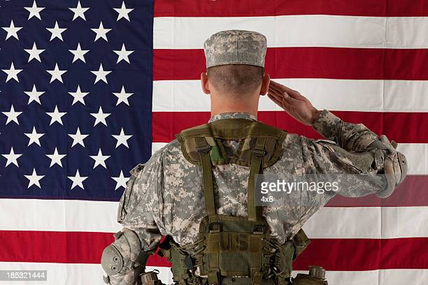 Army soldier saluting US flag