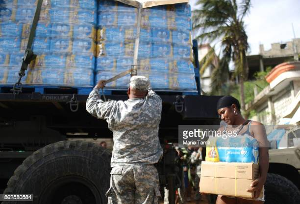 S Army soldier starts to unload a shipment of water provided by FEMA as a resident walks past in a neighborhood without grid electricity or running...