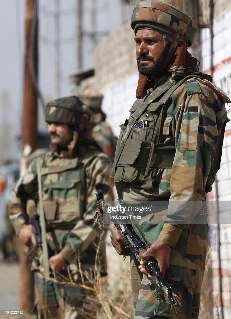 Army soldier take position near the site of a shootout after militants attacked a Border Security Force (BSF) convoy at Nowgam Srinagar- Jammu National Highway, on March 21, 2013 in Srinagar, India. Three BSF jawans were injured in the attack.