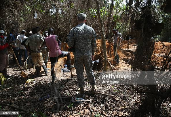 S Army soldier watches as a burial team prepares new graves outside an Ebola treatment center on October 7 2014 near Gbarnga in Bong County of...