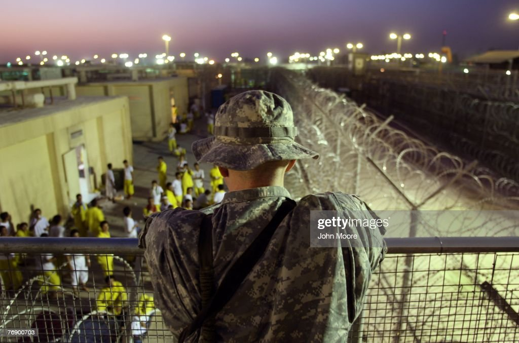 A U.S. Army soldier watches Iraqi detainees at the Camp Cropper detention center September 19, 2007 in Baghdad, Iraq. U.S. forces have a total of about 25,000 detainees in several centers in Iraq, up from only about 14,000 before the American troops surge this year. The detainee population includes insurgents from all anti-coalition groups in Iraq, Al Qaeda foreign fighters, criminals and many innocent Iraqis caught up in U.S. military raids. Military officials say they have instituted a new review process to more quickly identify the innocent detainees for release.