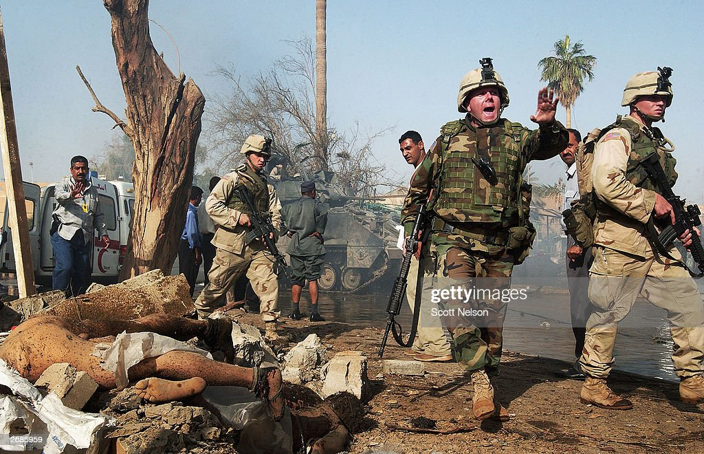 U.S. Army soldiers and Iraqi policemen walk past two bodies as they seal off the scene of a massive car bomb attack on the headquarters of the International Committee of the Red Cross (ICRC) October 27, 2003 in Baghdad, Iraq. The attack killed at least ten people and comes on the first day of the holy Islamic month of Ramadan.