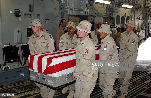 S Army soldiers assigned to the 10th Mountain Division load a flag draped coffin bearing the remains of a fellow soldier onto a transport plane at...