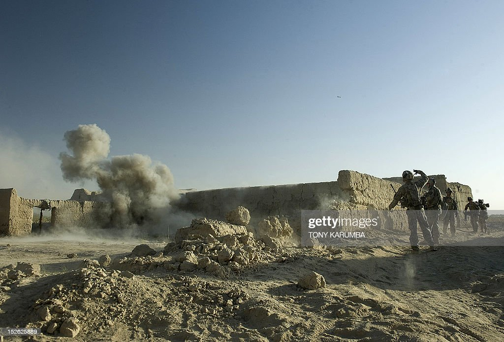 US Army soldiers attached to the 2nd platoon, C-Coy. 1-23 Infantry based at Zangabad foward operating base in Panjwai district hurls a grenade at a perimeter wall rigged with an IED trap to trigger a safe detonation of the bomb trap during a dawn operation at Naja-bien village on September 23, 2012. A total of 374 civilians were killed and 581 injured in August as a result of the war in Afghanistan, making it the second deadliest month for civilians since 2007, the United Nations said. AFP PHOTO/Tony KARUMBA