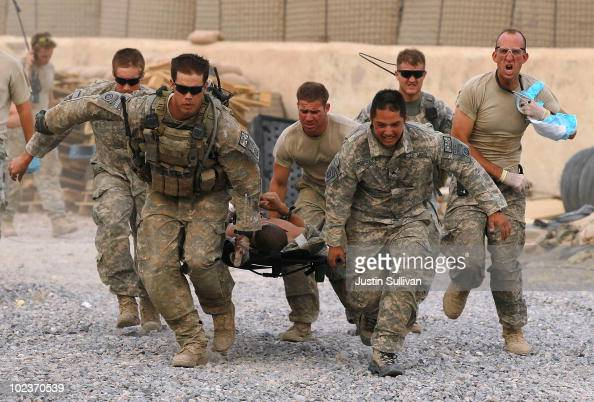 S Army soldiers carry a critically wounded American soldier on a stretcher to an awaiting MEDEVAC helicopter from Charlie Co Sixth Battalion 101st...