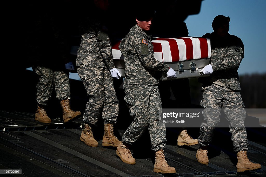 U.S. Army soldiers carry the flag-draped transfer case containing the remains of U.S. Army Sgt. David J. Chambers, during a dignified transfer at Dover Air Force Base, on January 19, 2013 in Dover, Delaware. Chambers, who was from Hampton, Va., was killed while supporting Operation Enduring Freedom.