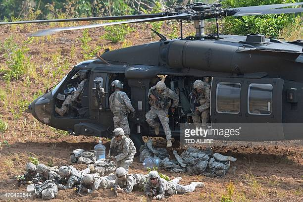 US army soldiers from 2nd Stryker Brigade Combat of the 5th Infantry Division based in Hawaii take their positions after disembarking from a UH60...