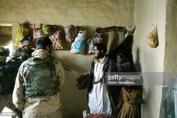 US Army soldiers from the 1st Battalion 501 Parachute Infantry Regiment confront family in a village about former Taliban suspects in the area and...