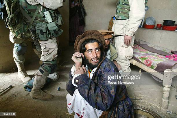 US Army soldiers from the 1st Battalion 501 Parachute Infantry Regiment confront a family in a village about former Taliban suspects in the area and...