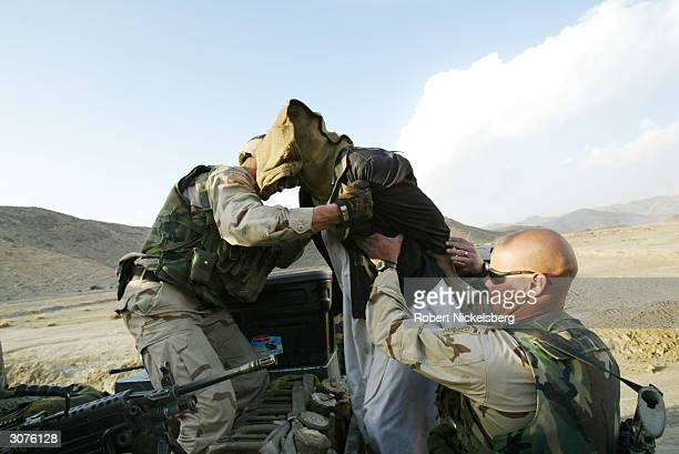 US Army soldiers from the 1st Battalion 501 Parachute Infantry Regiment help a suspected Afghan in for questioning after confronting a village family...