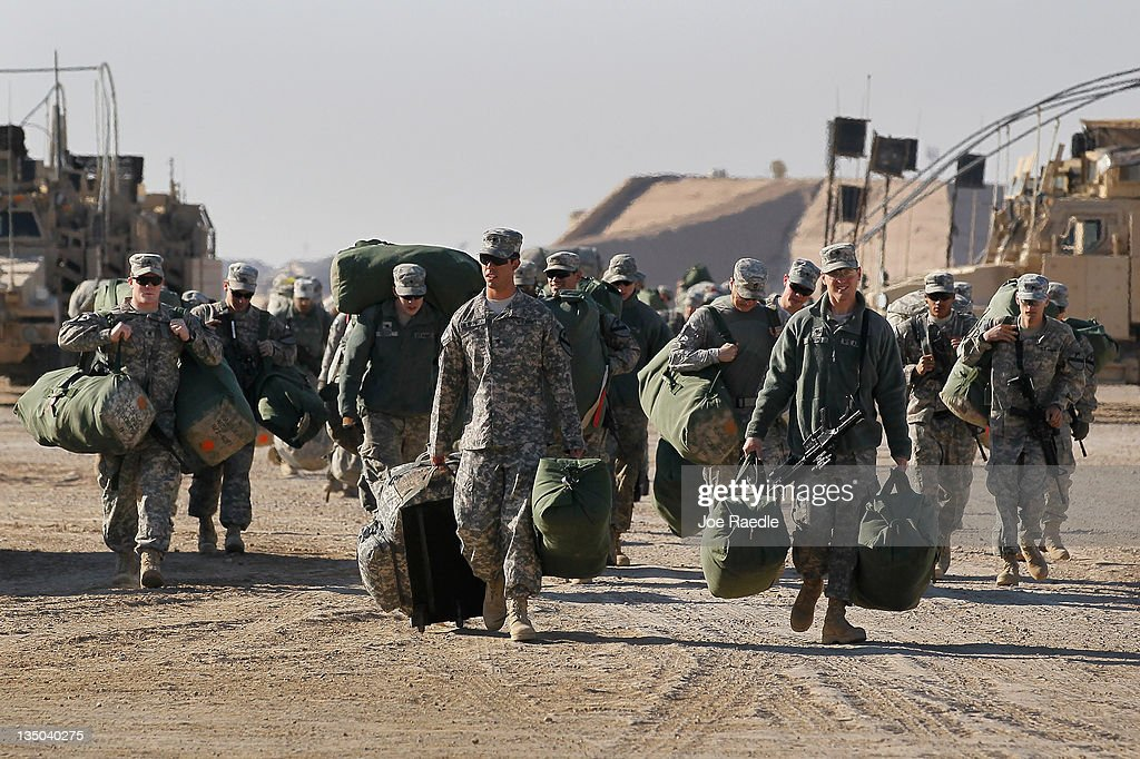 U.S. Army soldiers from the 2-82 Field Artillery, 3rd Brigade, 1st Cavalry Division, carry their bags to shipping containers as they prepare to leave Camp Adder as the base is readied to be handed back to the Iraqi government later this month on December 6, 2011 at Camp Adder, near Nasiriyah, Iraq. Camp Adder is one of the few bases remaining that the United States controls as America's military continues its pullout of the country by the end of this year, after eight years of war and the overthrow of Saddam Hussein.