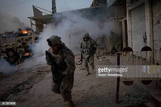 Army soldiers from the 3rd Brigade Combat Team 4th ID run back to their vehicles through smoke from an Iraqi Army position after a US Apache launched...
