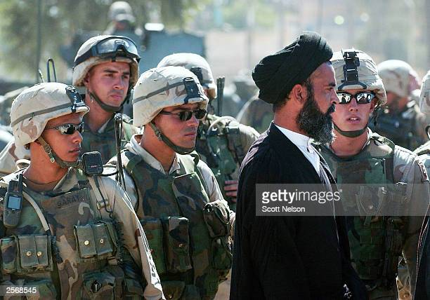 S Army soldiers gather around a local Iraqi Shia cleric as they negotiate with leaders of a protest against the detention of local Shia Imam Mo'ayed...