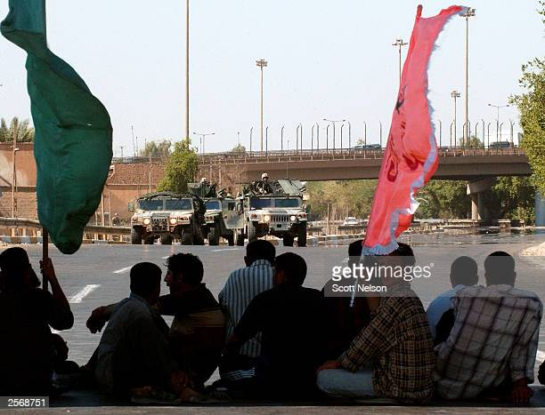 S Army soldiers in humvees keep a watchful eye over a Shia protest against the detention of local Shia Imam Sheik Mo'ayed alKhezragi October 7 2003...