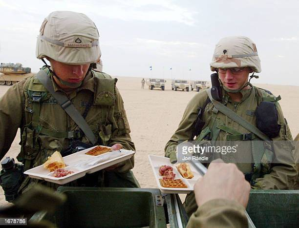 S Army soldiers line up for a hot breakfast December 9 2002 near the Iraqi border in Kuwait They are part of the Armored Task Force 464 that is...