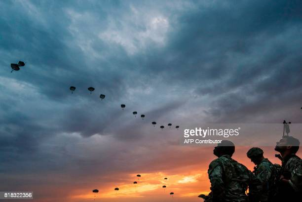 US Army soldiers look on while NATO paratroopers drop out of a US Air Force Hercules during the 'Swift Response 17' joint airborn military exercise...