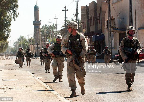 S Army soldiers move through a street in front of the alBaya'a mosque during a protest against the detention of local Shia Imam Mo'ayed alKhezragi by...