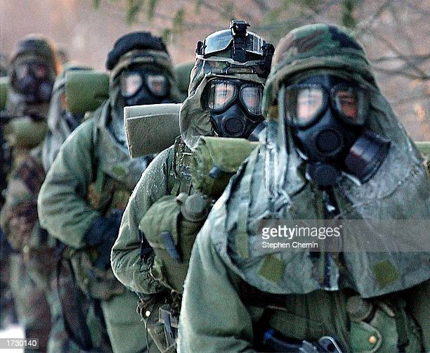 Army soldiers of the 110th Mountain Division wear protective gas masks as they march towards the nuclear biological and chemical warfare training...