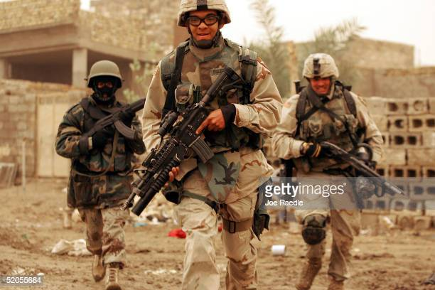 S Army soldiers of the 1st Battalion 503rd Infantry Regiment and an Iraqi commando run for cover as they conduct a joint patrol searching for...